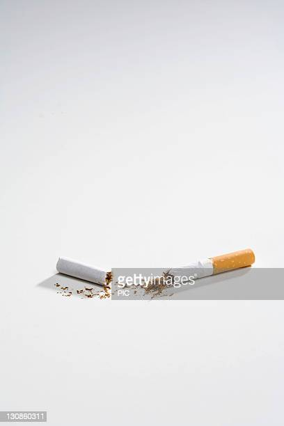 Broken cigarette split into two, split in half