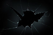 broken cracked glass with hole in black background