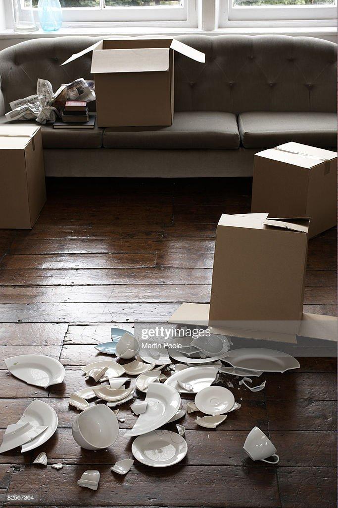 broken crockery next to cardboard box : Stock Photo