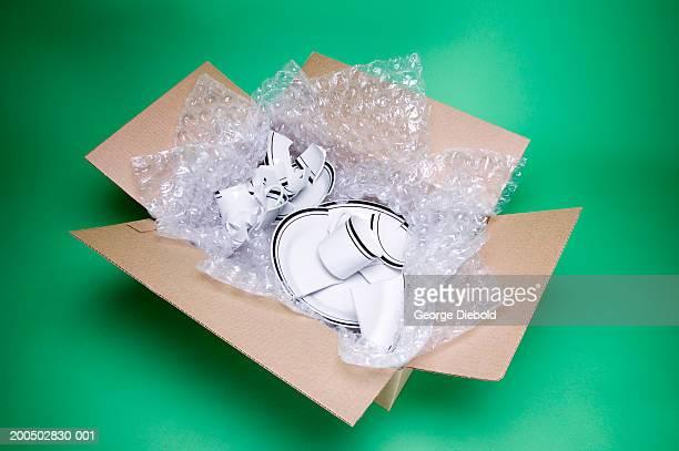 broken dishes in cardboard box - breekbaarheid stockfoto's en -beelden