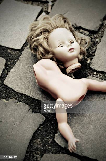 Broken Doll Lying on Cobblestone Ground
