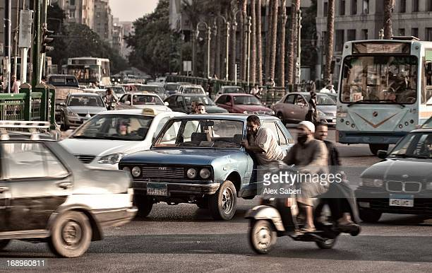 a broken down car is pushed through very busy cairo traffic. - alex saberi 個照片及圖片檔