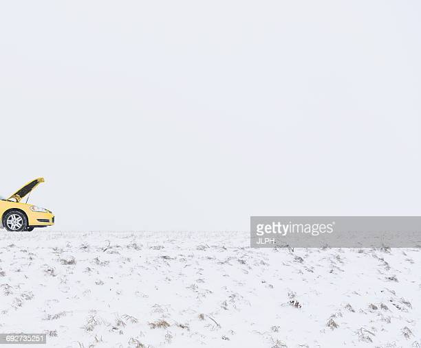 Broken down car on snow covered landscape