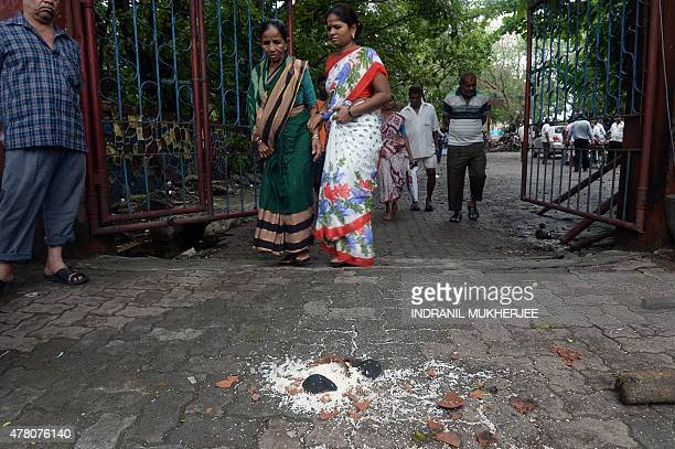 A broken earthen pot and rice is seen as relatives and mourners walk out of a Hindu crematorium after the the last rites of Shyam Dhotre who died...