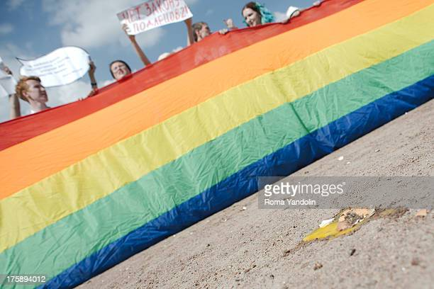 CONTENT] A broken egg lies in front of gay rights activists that hold a rainbow flag and shouts slogans during a Gay Pride parade in St Petersburg...