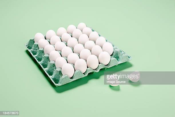 Broken egg next to egg carton