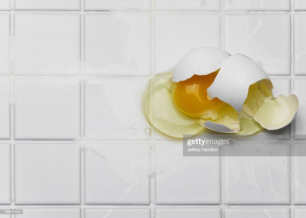 Broken egg on white tiles : Stock Photo