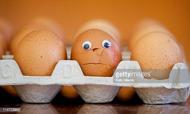 a broken egg with sad face - spoil system stock pictures, royalty-free photos & images