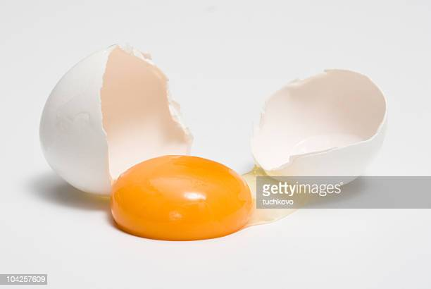 Broken eggshells next to egg yolk