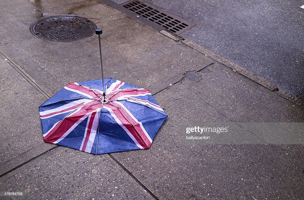 Broken English flag umbrella on ground : Stock Photo