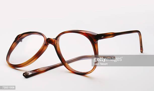 Broken eyeglasses on white background, close-up