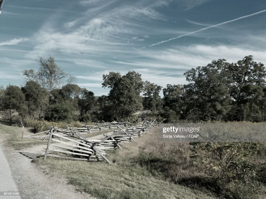 Broken fence near the country road : Stock Photo