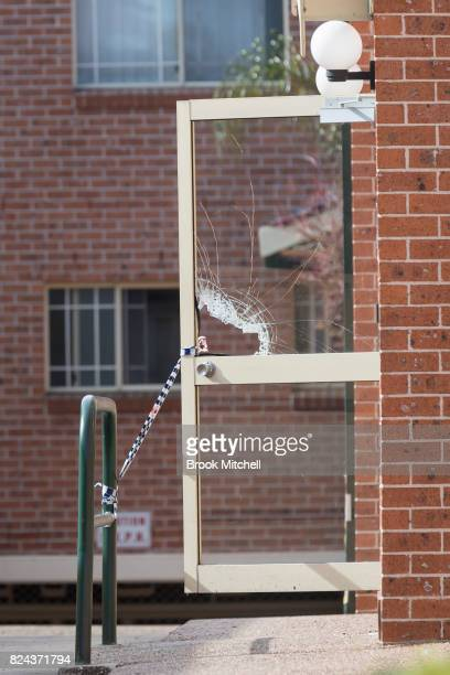 A broken glass door at the entrance to an apartment in Sproule Street Lakemba the scene of an overnight terror raid on July 30 2017 in Sydney...