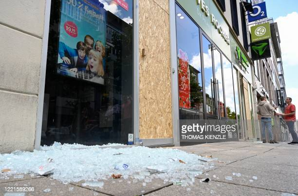 Broken glass lies on the pavement in front of a mobilephone shop in a pedestrian aerea in Stuttgart, southern Germany on June 21, 2020. - Hundreds of...