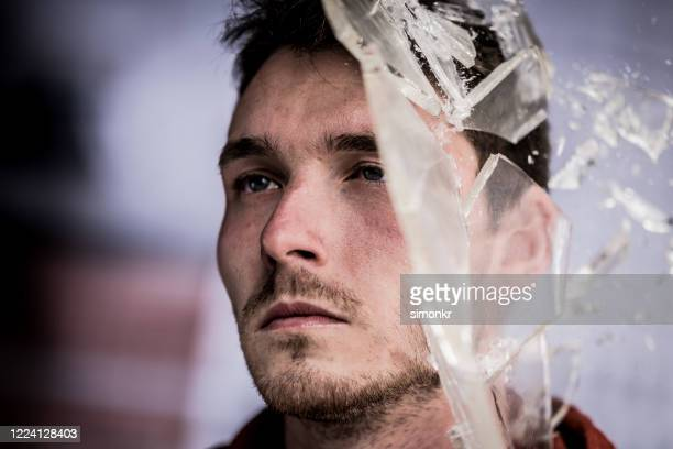 broken glass pieces shattering on man's face - only young men stock pictures, royalty-free photos & images