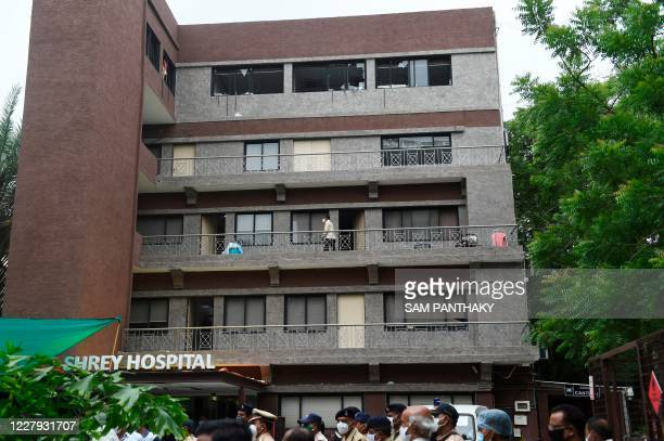 Broken glass windows are seen at the top floor f the Shrey Hospital after a fire broke early in the morning in the intensive care unit, in Ahmedabad...