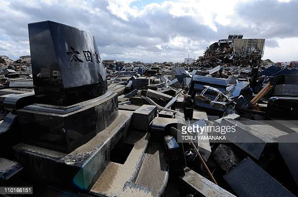 Broken gravestones lie on the ground in front of a Buddist temple damaged by the March 11 tsunami and earthquake in Natori in Miyagi Prefecture on...