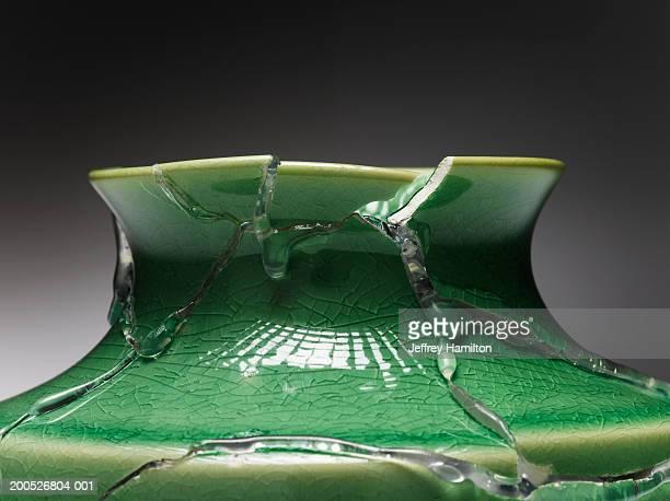 Broken green vase glued together, close-up (still life)
