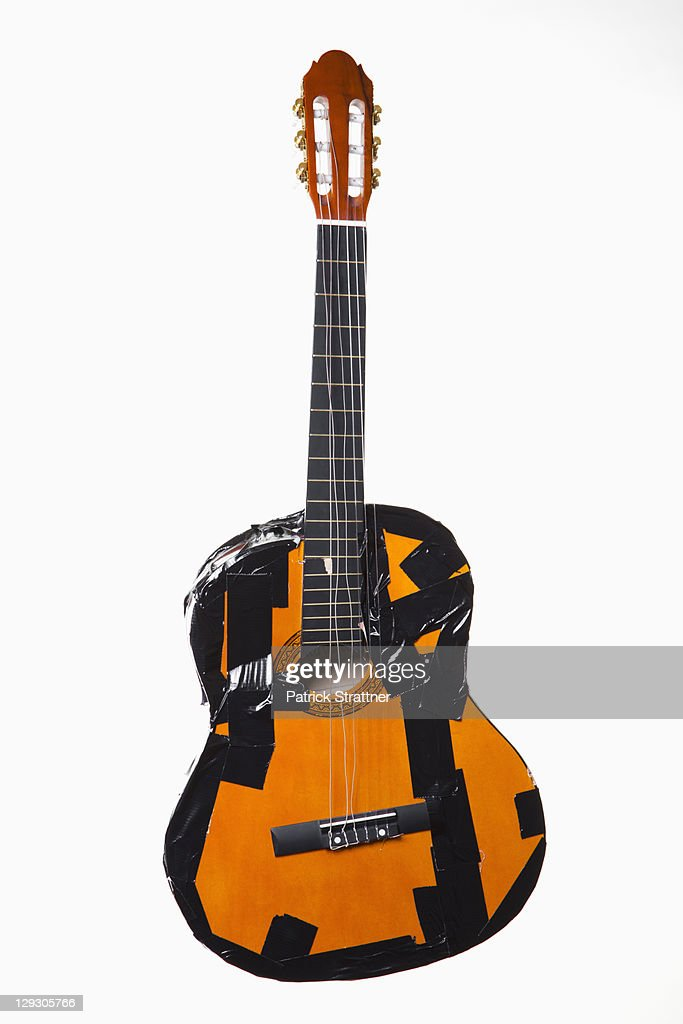 A broken guitar taped together with duct tape : Stock Photo