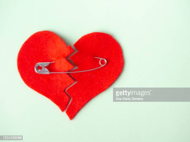 a broken heart sewn with safety pins against green background. heartbreak concept - broken heart stock pictures, royalty-free photos & images