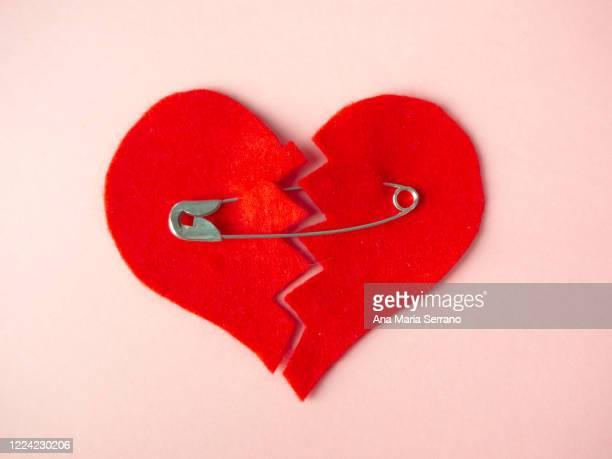 a broken heart sewn with safety pins against pink background. heartbreak concept - verhältnis stock-fotos und bilder