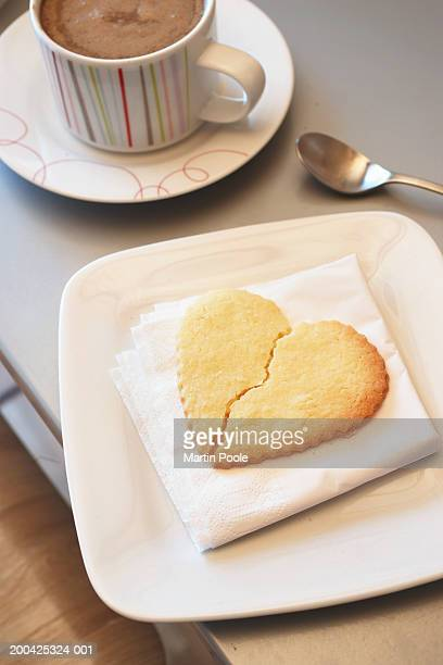 Broken heart shaped biscuit on dish by cup of coffee