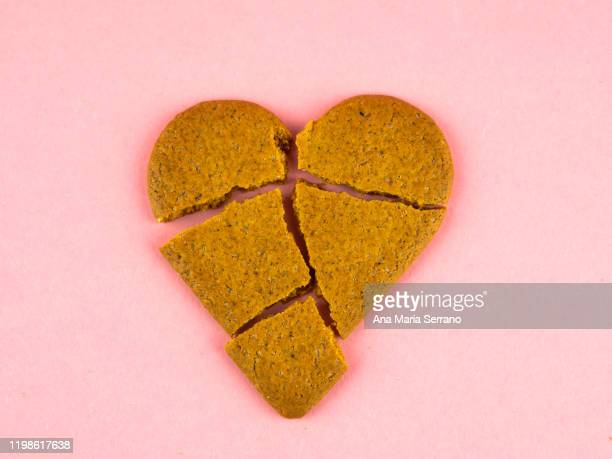 a broken heart shaped ginger cookie. heartbreak concept - broken heart stock pictures, royalty-free photos & images