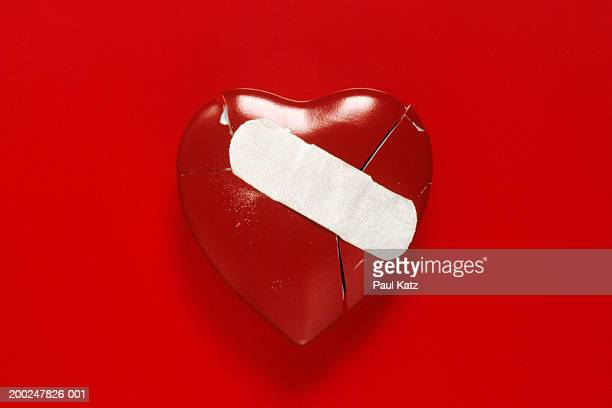 broken heart with band aid - bandage stock photos and pictures