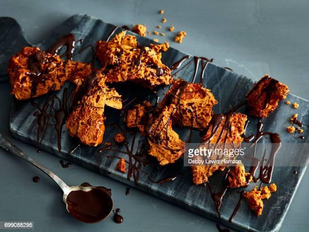 broken honeycomb toffee with melted chocolate garnish on marble cutting board - caramelo de manteiga comida doce imagens e fotografias de stock