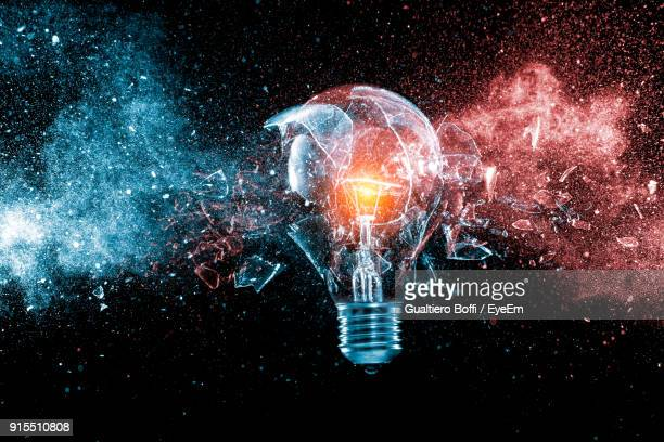 broken illuminated light bulb against black background - light bulb stock pictures, royalty-free photos & images