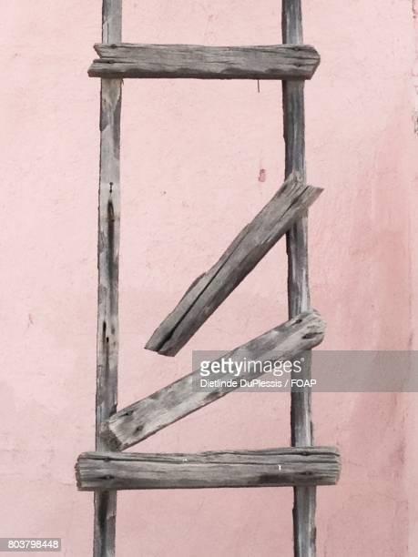 Broken ladder against wall