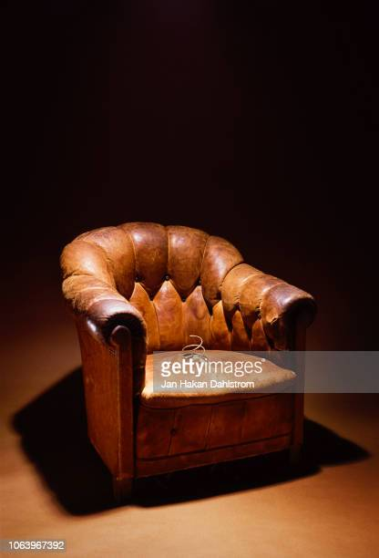 broken leather-upholstered armchair - armchair stock pictures, royalty-free photos & images