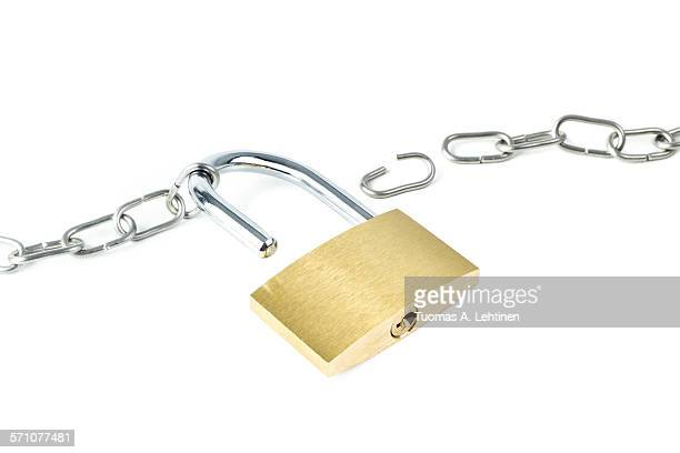 Broken metal chain and an unlocked padlock