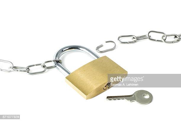 Broken metal chain, locked padlock and a key