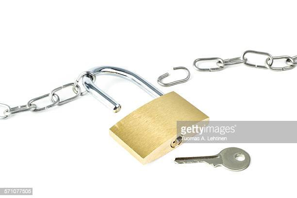 Broken metal chain, unlocked padlock and a key