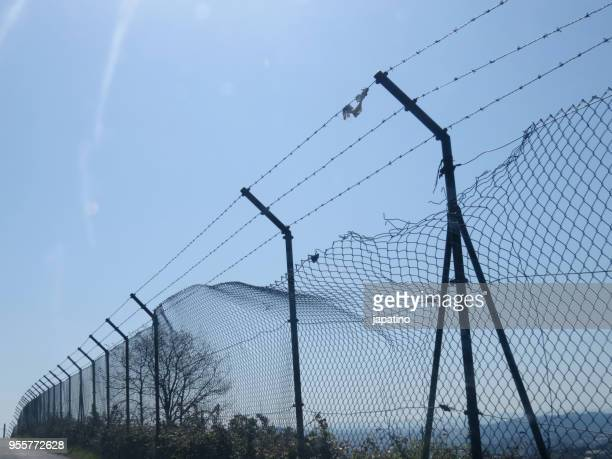 broken metal fence against illegal immigrants - crossing sign stock pictures, royalty-free photos & images