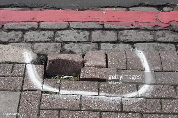 Broken pavement damaged sidewalk kerb raised bricks marked for repair