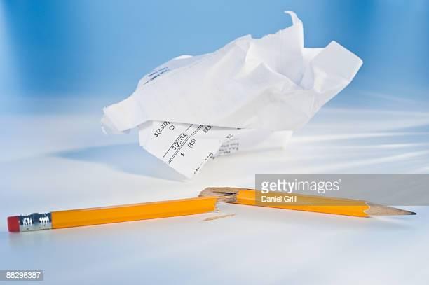 Broken pencil and crumpled paper
