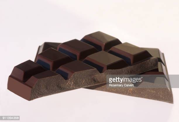 broken pieces from a large dark chocolate bar, on white. - dark chocolate stock pictures, royalty-free photos & images