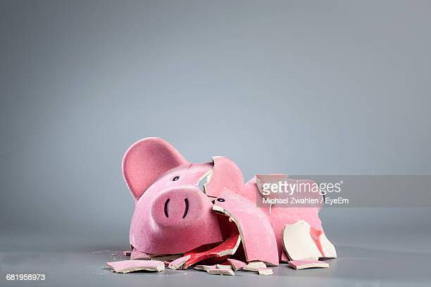 broken piggy bank against gray background - shattered glass stock pictures, royalty-free photos & images