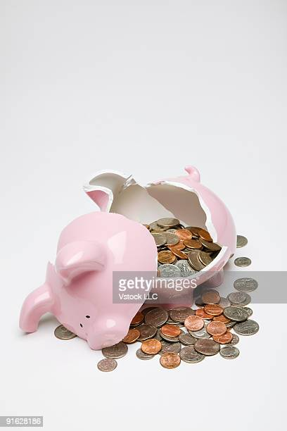 A broken piggy bank with coins