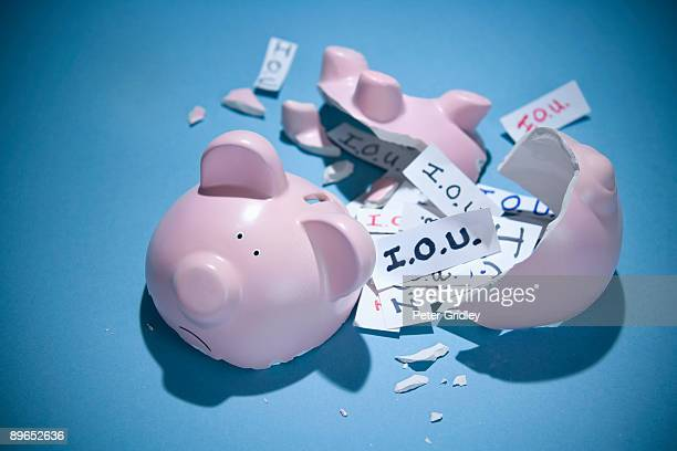 Broken piggy bank with many I.O.U. notes