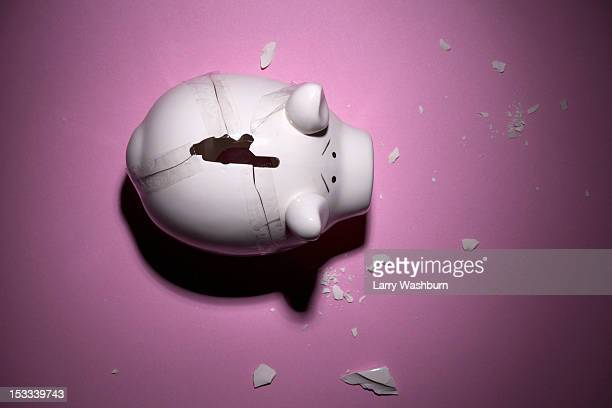 A broken piggy bank with pieces taped back together