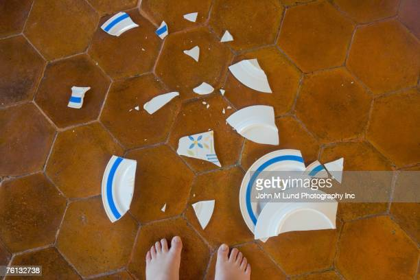 Broken plate next to child's bare feet