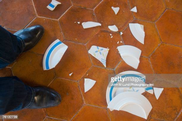 Broken plate next to man's feet