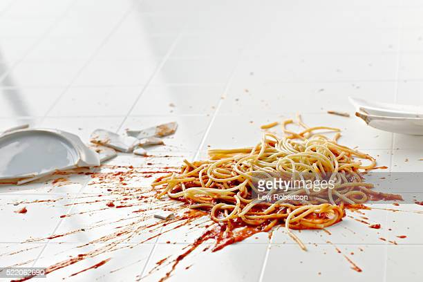 Broken plate of spaghetti on floor