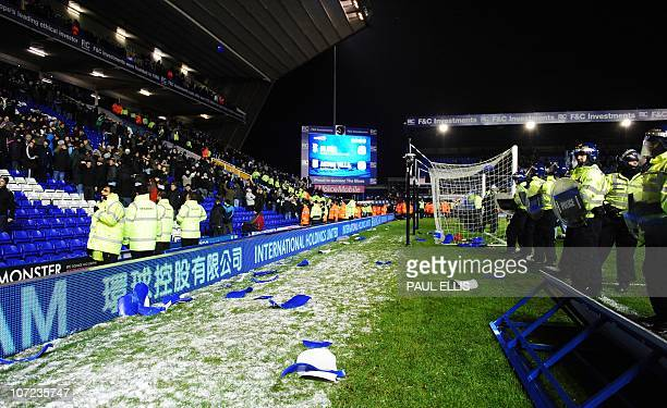 Broken seats lie between police officers and Aston Villa fans after the English Football League Cup football match betwen Birmingham City and Aston...
