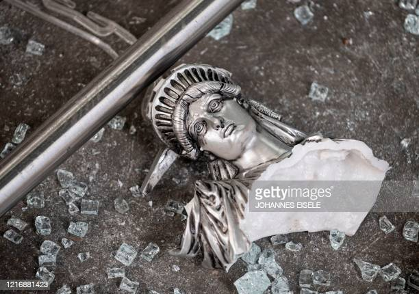 TOPSHOT A broken Statue of Liberty figure is seen between glass shatters outside a looted souvenir shop after a night of protest over the death of an...