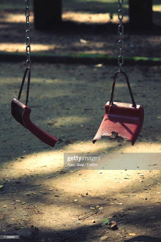 Broken Swing Hanging At Playground : Stock Photo