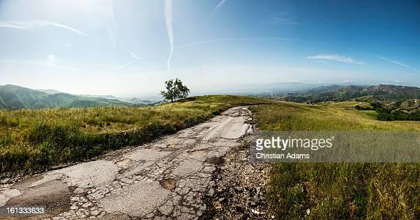 broken tar road - strada di campagna foto e immagini stock